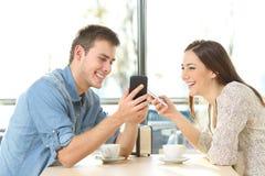 Pares que comparten el medios contenido con los teléfonos elegantes Imágenes de archivo libres de regalías