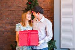 Pares que comparten el regalo de Navidad Familia joven que abraza y que sostiene la caja de regalo roja en casa con las decoracio Fotos de archivo