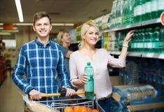 Pares que compram a água mineral Fotografia de Stock