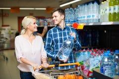Pares que compram a água mineral Foto de Stock Royalty Free
