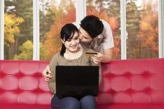 Pares que compran en línea con la computadora portátil Fotografía de archivo
