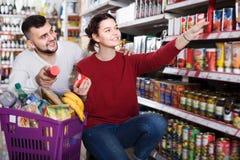 Pares que compran la comida enlatada en la tienda de ultramarinos Imagen de archivo