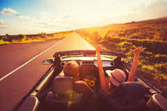 Pares que conducen el convertible en la puesta del sol