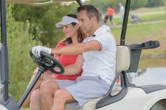Pares que conduzem o carrinho do golfe no campo de golfe imagem de stock