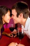 Pares que consiguen más cercanos mientras que comiendo vino Imagen de archivo libre de regalías