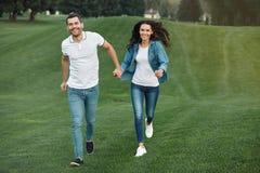 Pares que correm na grama verde no parque foto de stock royalty free