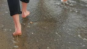 Pares que corren descalzo a través del agua almacen de metraje de vídeo