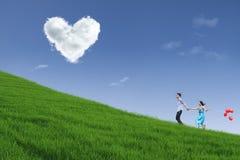 Pares que corren en la colina con la nube del corazón Fotografía de archivo