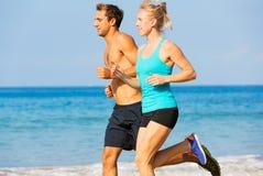 Pares que corren en la playa Foto de archivo libre de regalías