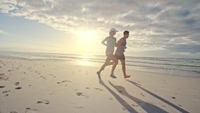 Pares que corren a lo largo de la playa por mañana metrajes