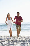 Pares que corren a lo largo de Sandy Beach Holding Hands Imagen de archivo libre de regalías