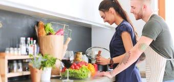 Pares que cozinham junto em sua cozinha em casa fotografia de stock