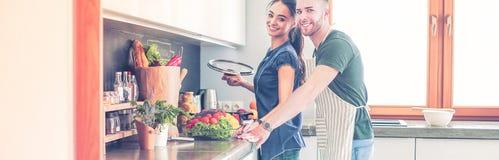 Pares que cozinham junto em sua cozinha em casa fotografia de stock royalty free