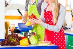 Pares que cozinham no alimento saudável da cozinha doméstica Imagens de Stock