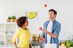 Pares que cozinham o alimento e que manipulam tomates em casa Foto de Stock