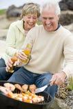 Pares que cozinham o assado em uma praia Imagem de Stock Royalty Free