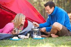 Pares que cozinham o café da manhã no feriado de acampamento fotografia de stock