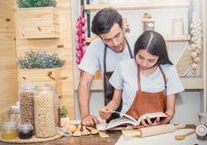 Pares que cozinham o jantar em sua cozinha Imagem de Stock Royalty Free