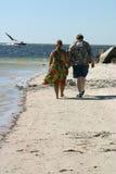 Pares que dan un paseo en la playa Imágenes de archivo libres de regalías