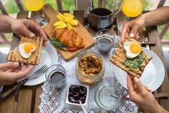 Pares que desayunan en el balcón Desayuno con la tostada, el atasco y el café imagen de archivo