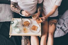 Pares que desayunan junto en cama Imagenes de archivo