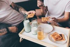 Pares que desayunan junto en cama Foto de archivo