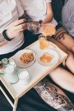 Pares que desayunan junto en cama Fotos de archivo