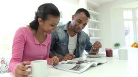 Pares que desayunan y que leen la revista en cocina almacen de video