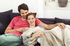 Pares que descansam no sofá na sala de visitas Imagens de Stock