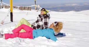 Pares que descansan sobre la colina después de esquiar metrajes