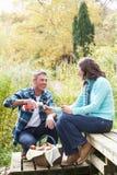 Pares que disfrutan de comida campestre al aire libre en arbolado del otoño imagen de archivo