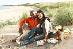 Pares que disfrutan de comida campestre en la playa junto Fotos de archivo