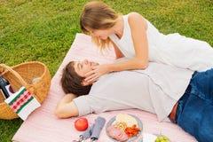 Pares que disfrutan de comida campestre romántica de la puesta del sol Imagen de archivo