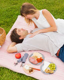 Pares que disfrutan de comida campestre romántica de la puesta del sol Foto de archivo