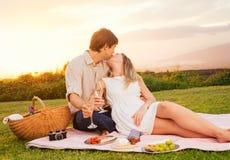 Pares que disfrutan de comida campestre romántica de la puesta del sol Imagenes de archivo