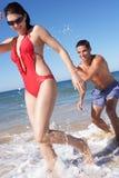 Pares que disfrutan de día de fiesta de la playa Imágenes de archivo libres de regalías