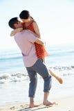 Pares que disfrutan de día de fiesta romántico de la playa fotografía de archivo