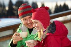 Pares que disfrutan de la bebida caliente en café en la estación de esquí Imagenes de archivo