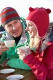 Pares que disfrutan de la bebida caliente en café en la estación de esquí imagen de archivo libre de regalías