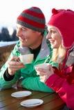 Pares que disfrutan de la bebida caliente en café en la estación de esquí fotos de archivo