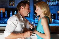 Pares que disfrutan de la bebida en barra Imagenes de archivo
