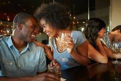 Pares que disfrutan de la bebida en la barra con los amigos fotografía de archivo