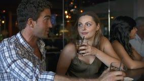 Pares que disfrutan de la bebida en la barra junto almacen de metraje de vídeo