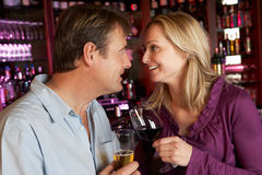 Pares que disfrutan de la bebida junto en barra Fotos de archivo