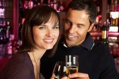Pares que disfrutan de la bebida junto en barra fotos de archivo libres de regalías