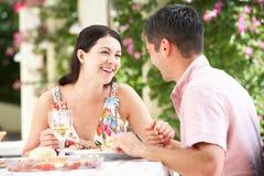 Pares que disfrutan de la comida al aire libre Fotos de archivo