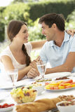 Pares que disfrutan de la comida al aire libre en jardín Imágenes de archivo libres de regalías