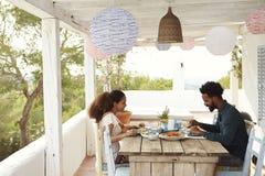 Pares que disfrutan de la comida al aire libre en terraza junto Imagenes de archivo