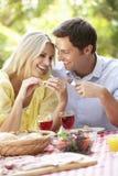 Pares que disfrutan de la comida al aire libre junto Fotografía de archivo libre de regalías