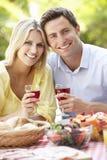 Pares que disfrutan de la comida al aire libre junto Imagen de archivo libre de regalías